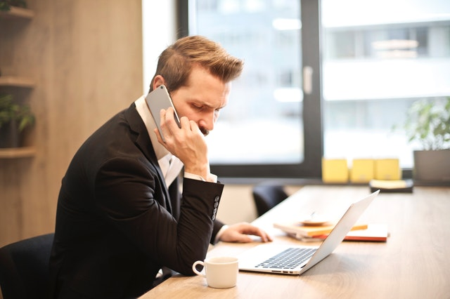 man having a phone call in front of a laptop 859264 - Corporate Recovery